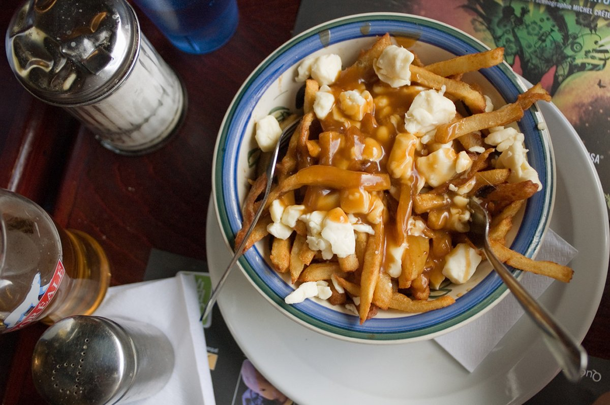 chow-down-on-poutine-a-dish-of-crisp-french-fries-with-brown-gravy-and-cheese-curds-in-montreal-locals-recommend-the-poutine-from-la-banquise