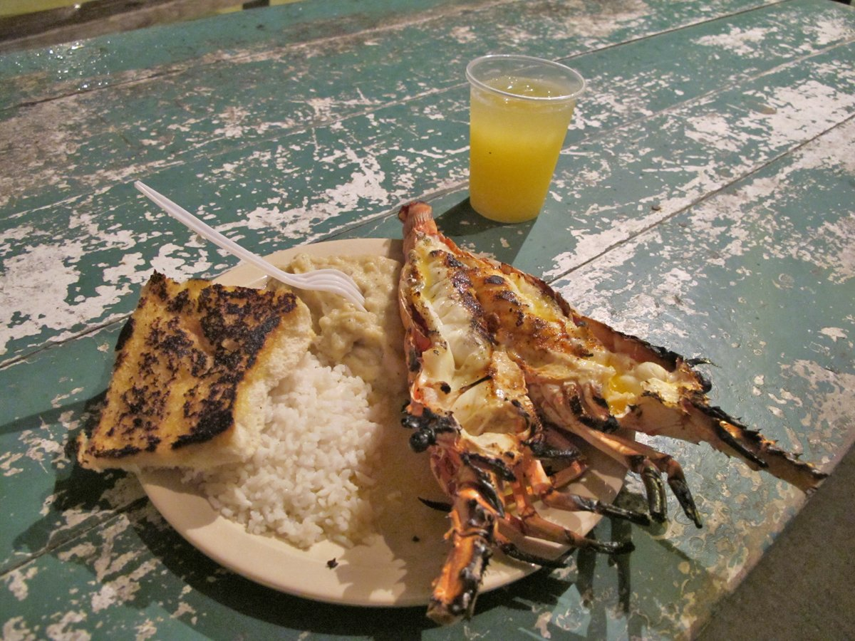 crack-open-a-fresh-grilled-lobster-right-on-the-beach-in-caye-caulker-belize